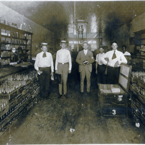 Percy Poston - center - holding a can in store - circa 1920.jpg